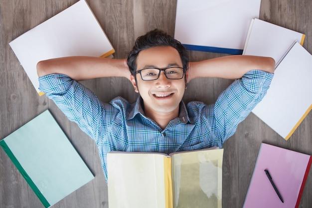 Menino estudante asiático feliz deitado no assoalho entre livros