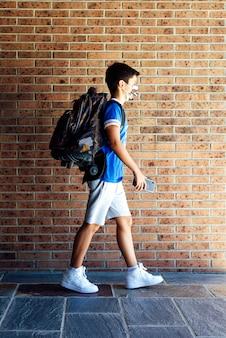 Menino estudante com máscara caminhando ao ar livre