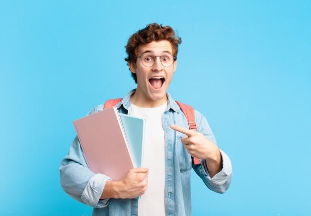 Menino estudante parecendo animado e surpreso, apontando para o lado e para cima para copiar o espaço