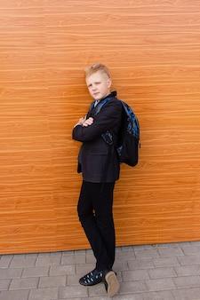 Menino estudante perto da escola na rua