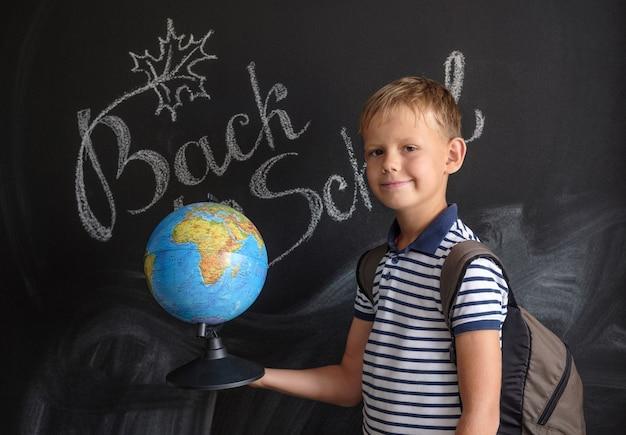 Menino europeu com globo físico no quadro escolar negro com inscrição de volta às aulas