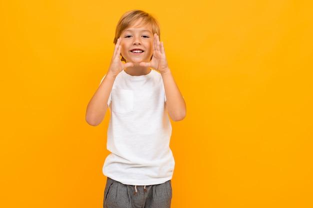 Menino europeu em uma camiseta branca grita em uma parede laranja com espaço de cópia
