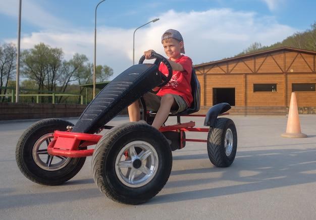 Menino europeu fofo andando de carro infantil com pedais no circuito no verão