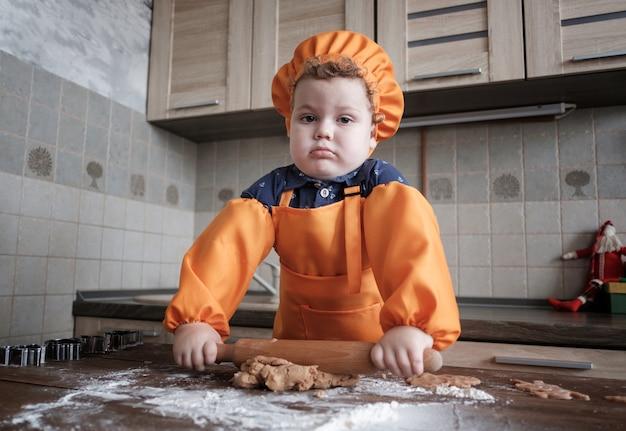 Menino europeu fofo com um boné de chef e avental preparando biscoitos de gengibre na cozinha, à mesa