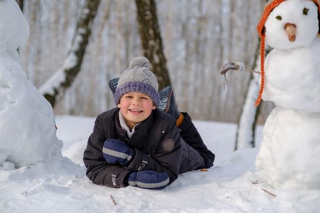Menino europeu fofo e o boneco de neve engraçado na floresta com neve em um dia de inverno na neve