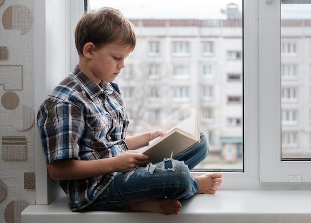 Menino europeu lendo um livro sentado no parapeito da janela