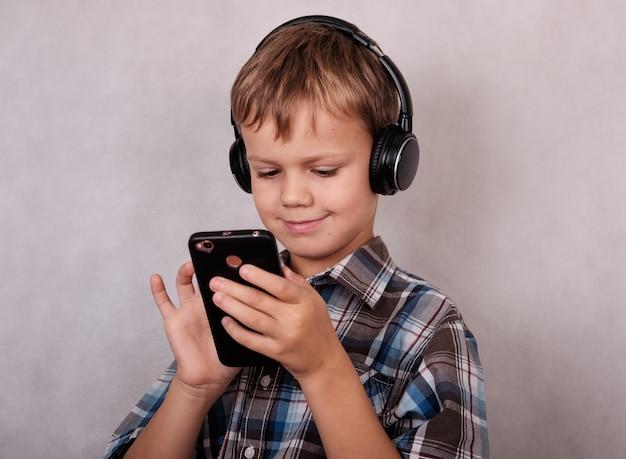 Menino europeu ouvindo música em fones de ouvido com um telefone celular por meio de uma conexão sem fio.