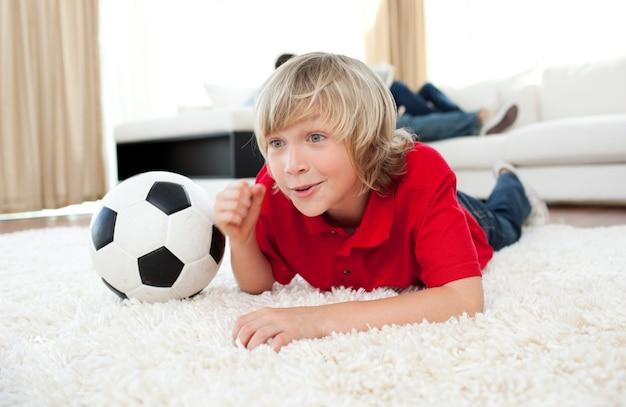 Menino excitado assistindo jogo de futebol deitado no chão