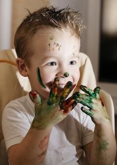 Menino excitado brincando com tintas de dedo
