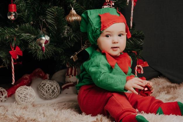 Menino fantasiado de elfo senta-se debaixo de uma árvore de natal com bolas