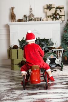 Menino fantasiado de papai noel monta um carro de brinquedo vermelho