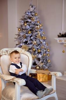 Menino fantasiado esperando o natal perto da árvore de natal
