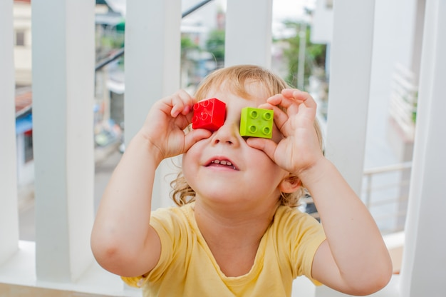 Menino faz olhos de blocos infantis coloridos. garoto menino bonitinho de óculos, brincando com muitos blocos de plástico coloridos internos. promoção de habilidades e criatividade