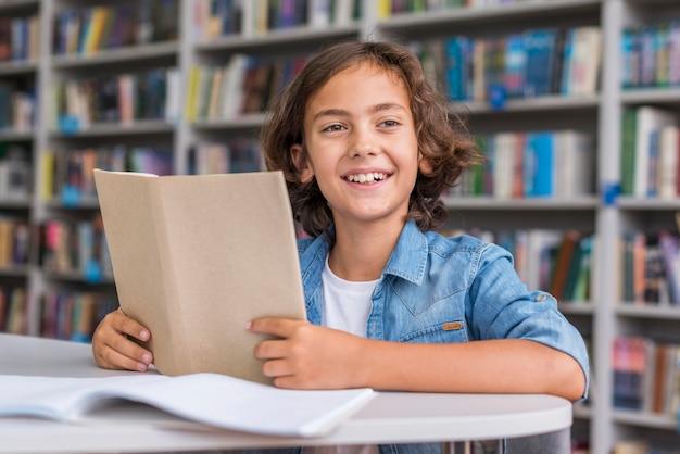 Menino fazendo a lição de casa na biblioteca