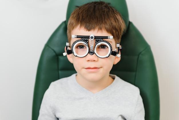 Menino fazendo exame de vista com óculos em clínica médica