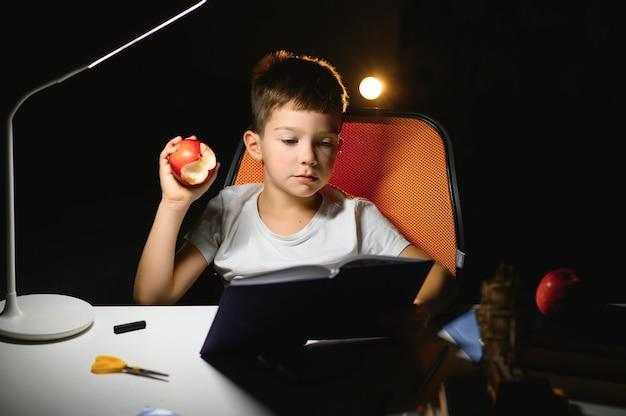 Menino fazendo lição de casa em casa à noite