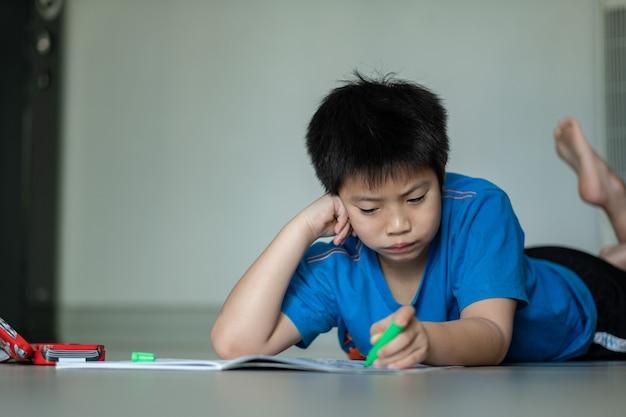 Menino fazendo lição de casa, papel de escrita infantil, conceito de educação, volta às aulas