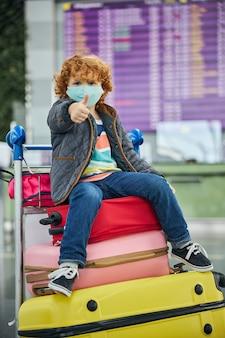 Menino fazendo sinal de positivo enquanto fica em cima das malas