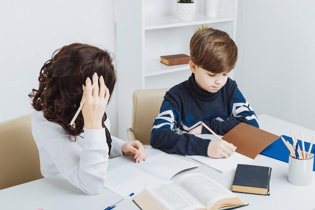Menino fazendo sua lição de casa e sua mãe o ajuda.