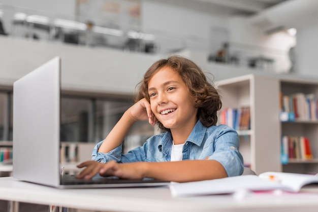 Menino fazendo sua lição de casa em um laptop na biblioteca