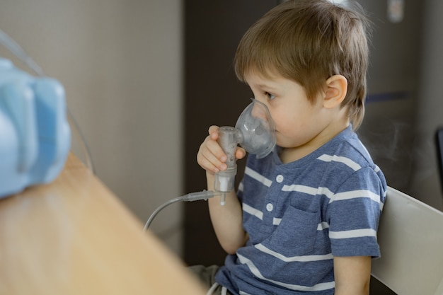 Menino fazendo terapia de inalação respiratória com nebulizador enquanto assiste desenhos ao telefone