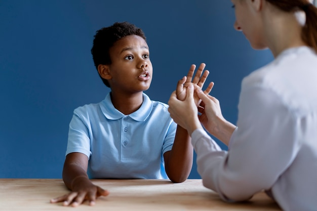 Menino fazendo uma sessão de terapia ocupacional com uma psicóloga