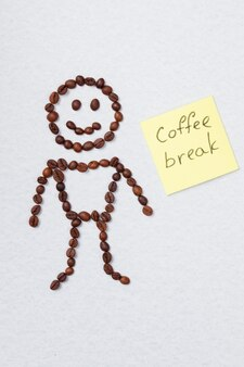 Menino feito de grãos de café isolados no branco. conceito de pausa para o café.