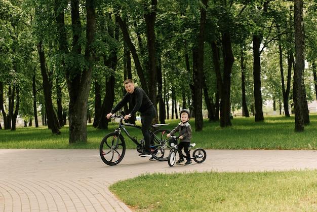 Menino feliz anda de bicicleta com um jovem pai no parque