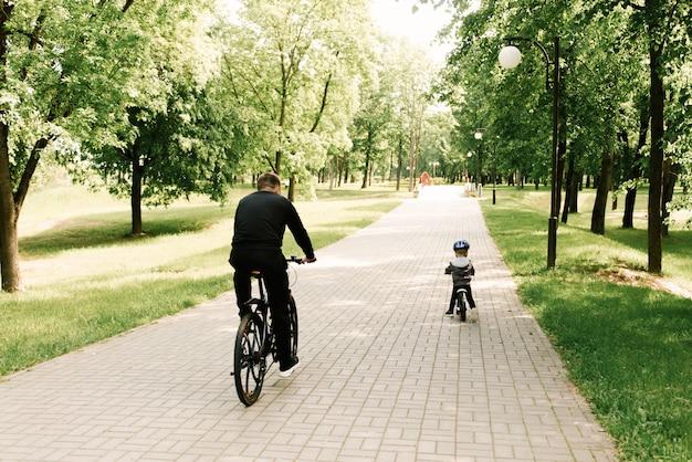 Menino feliz andando de bicicleta com o pai no parque