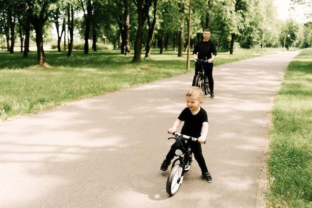 Menino feliz andando de bicicleta com um jovem pai no parque