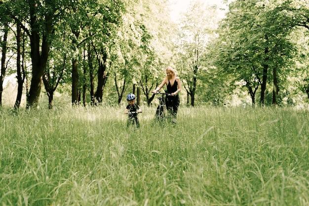 Menino feliz andando de bicicleta com uma jovem mãe no parque