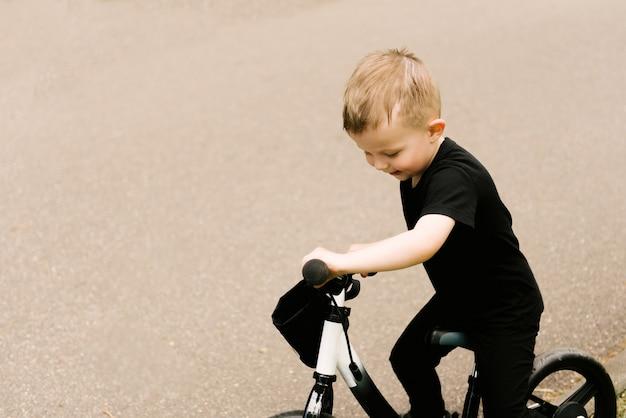 Menino feliz andando de bicicleta correndo no parque