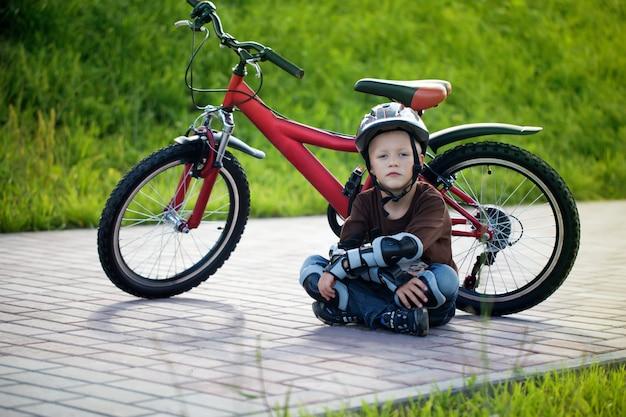Menino feliz, andar de bicicleta no parque à tarde