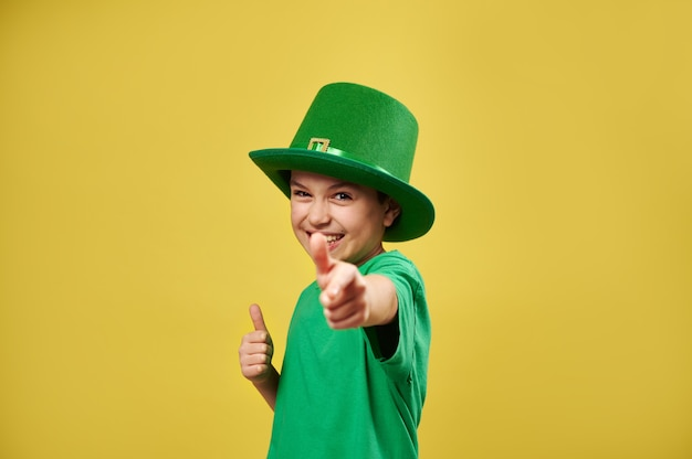 Menino feliz apontando a arma e mostrando o polegar para a câmera isolada na superfície amarela