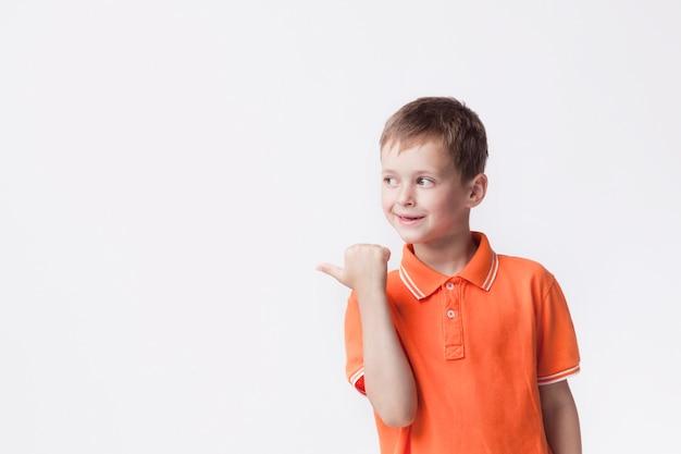 Menino feliz, apontando ao lado com o polegar no fundo branco
