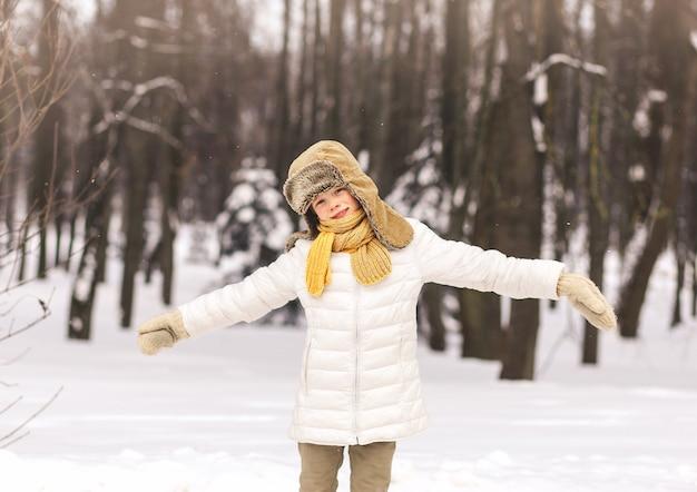 Menino feliz brinca no inverno no parque em um dia ensolarado
