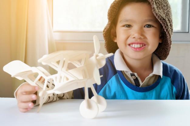 Menino feliz brincando com avião de brinquedo, pequeno garoto asiático goza de viagem, conceito de viagem e aventura