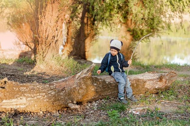 Menino feliz brincando no toco de madeira durante um passeio na floresta