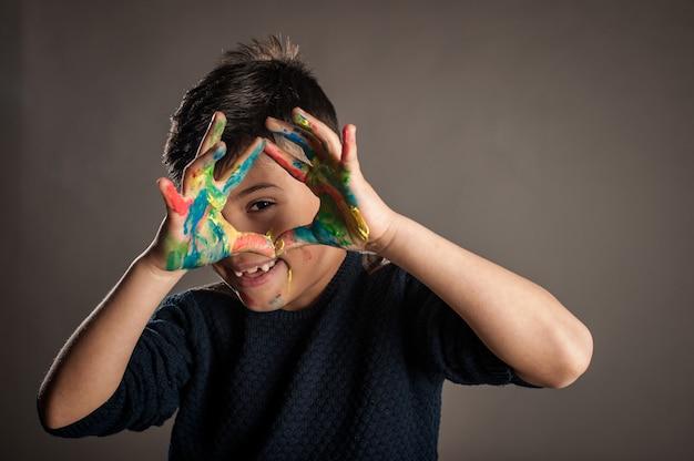 Menino feliz, com as mãos pintadas sobre um fundo cinza