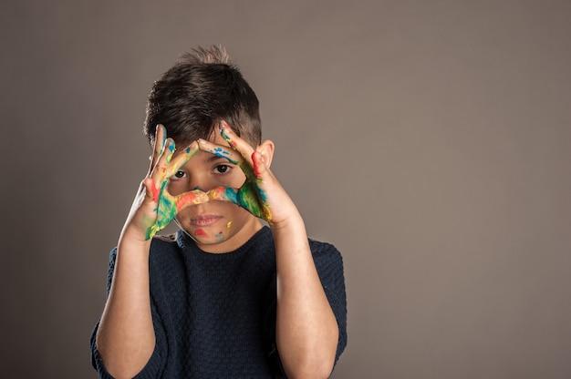 Menino feliz com as mãos pintadas