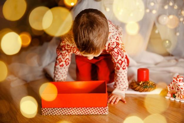 Menino feliz com caixa de presente de natal brincando perto da árvore de natal