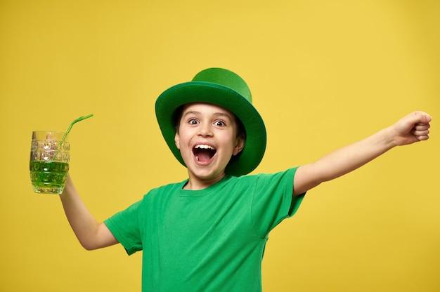 Menino feliz com camiseta verde e chapéu de duende com as mãos para cima segura um copo com bebida verde e expressa felicidade comemorando o dia de são patrício
