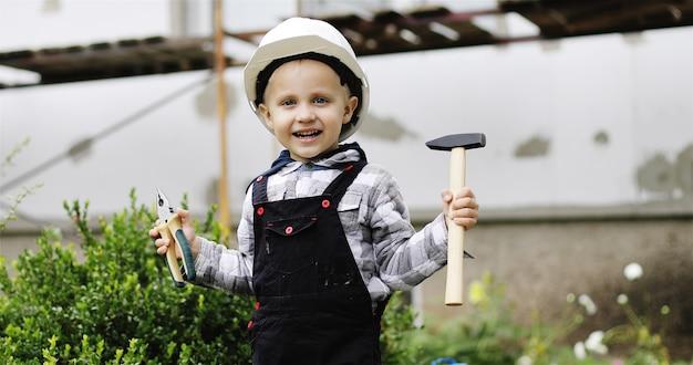 Menino feliz com capacete branco brincando com ferramentas em um canteiro de obras.