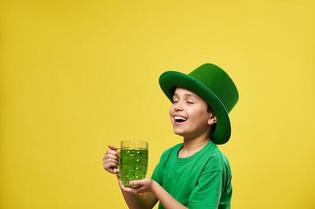 Menino feliz com chapéu de duende, desfrutando de uma bebida verde em pé em um fundo amarelo com espaço de cópia