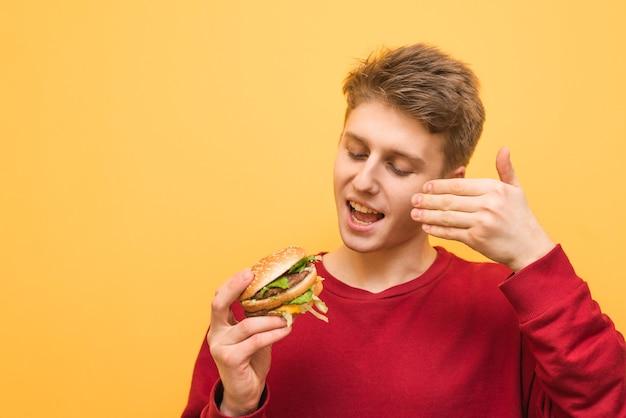 Menino feliz com hambúrguer nas mãos inala o cheiro de fast food fresco e sorri em um amarelo