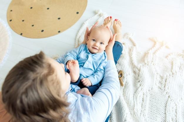 Menino feliz com menos de 1 ano de idade deitado nas mãos da mãe em close up do quarto. vista do topo. maternidade