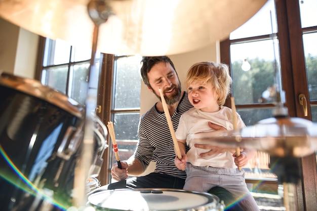 Menino feliz com o pai dentro de casa em casa, tocando bateria.