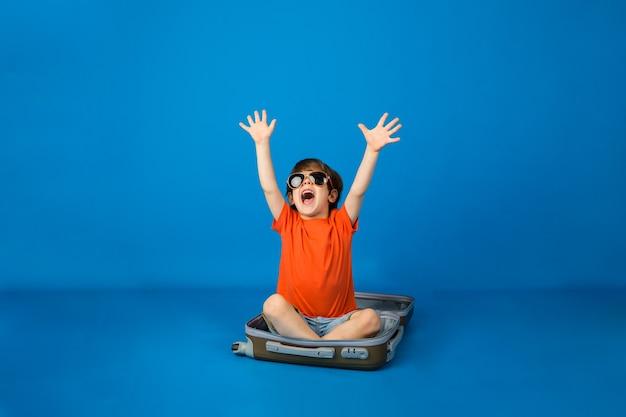 Menino feliz com óculos escuros sentado em uma mala em uma superfície azul com espaço para texto