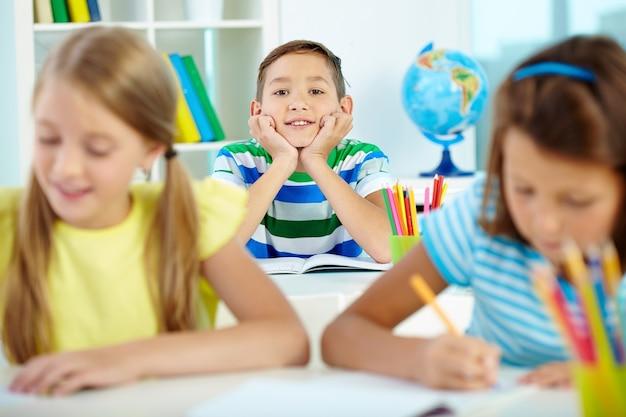Menino feliz com os amigos estudando
