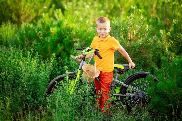 Menino feliz com roupas laranja, sentado em uma bicicleta na grama verde no verão